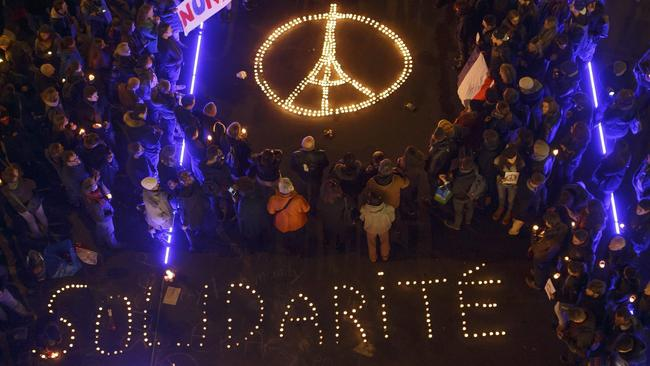 People standing in solidarity with France around a lighted image of the Eiffel Tower - the symbol of France